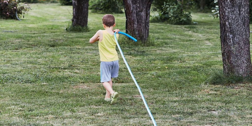 child taking garden hose across large field