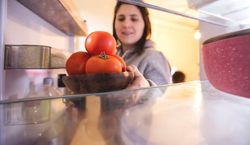 Woman putting tomatoes in refrigerator