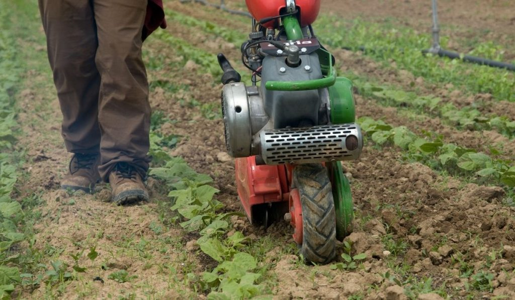 a man using a machine for tilling the soil