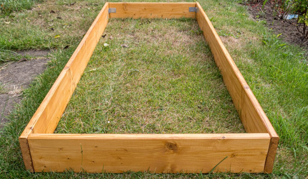 A newly built wooden raised bed stand empty on the lawn