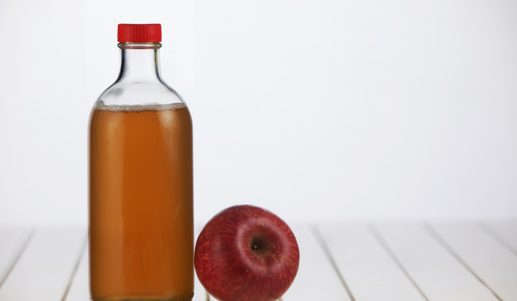 Apple cider vinegar with an apple on a blurry background.