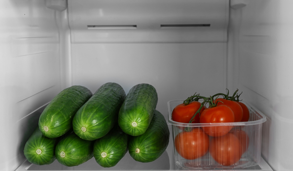 cucumber inside the ref, beside a bowl of fresh tomatoes